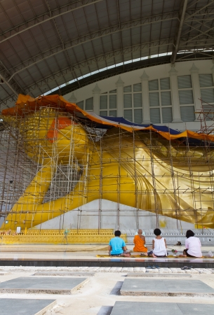 Women pray with faith, the presence of a large reclining Buddha, golden Buddha  Generally in Thailand, any kind of art decorated in Buddhist church, temple pavilion, temple hall, monk's house etc  creaced with money donated by people to hire artist  The