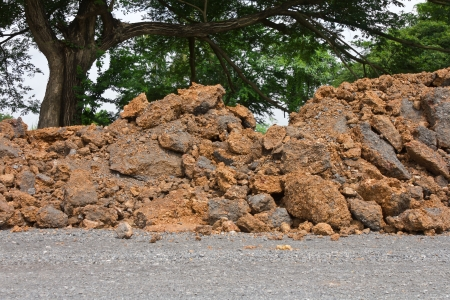 Large surface of the soil prepared to repair roads in rural areas with large trees in the background  photo