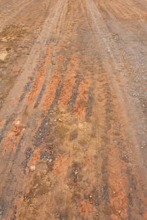 Surface of the ground at a rural road in the rain stops and traces its wheels  photo