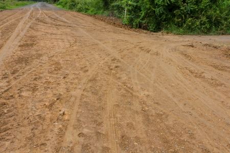 Traces of the wheels of cars and motorcycles on the roads in rural areas on the ground after a rain  photo