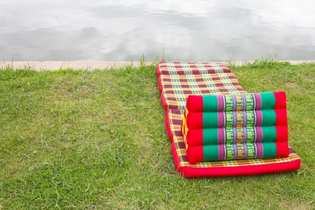 watershed: Triangular pillows and mattresses are placed on a beautiful pattern on the grass beside the pond  Stock Photo