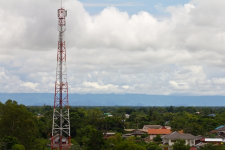 Telecommunications pole in community with trees and cloudy sky in the background  photo
