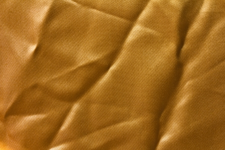 Surface has a wrinkled golden cloth and reflection of sunlight  photo