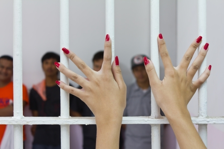 waiting convict: Woman fingers with red nails holding grip on the bars of the cage with the accused  Stock Photo