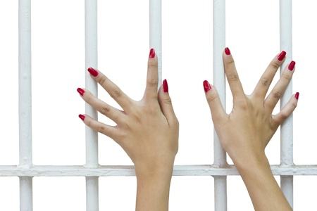 Isolates of woman fingers with red nails holding grip on the bars of the cage