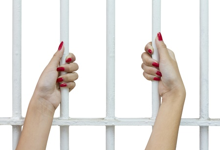 Isolates of woman fingers with red nails holding grip on the bars of the cage   photo