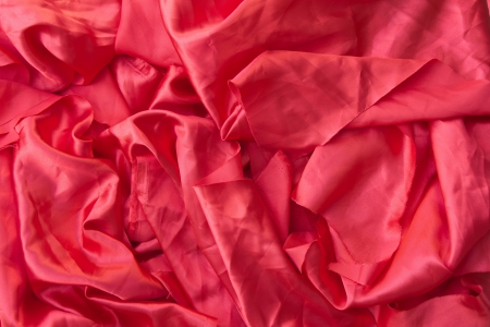 Background texture crumpled piece of red cloth with the rest of the sewing  photo