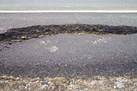 Broken asphalt in the pavement along the edge of the road on the gravel ground  photo