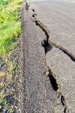 fissure: Side view asphalt road broken due to collapsing ground until the grass grows