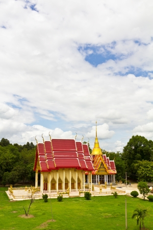 High view of the church and a Buddhist pagoda in the temple of Thailand, located in the grass near the tree  Stock Photo - 20591872