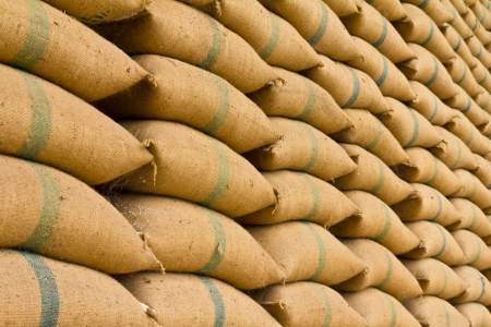 Old hemp sacks containing rice placed profoundly stacked in a row to keep up