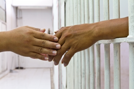 Female hand holding the hand of her husband, who was incarcerated in the prison bars of white  Stock Photo