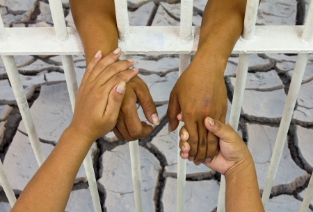 Hands holding hands women men trapped in prison with cracked soil as a backdrop  Stock Photo