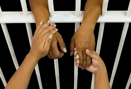 Her hands in the hands of the husband who was incarcerated