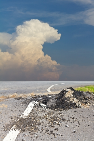 Demolished asphalt surface with clouds and sky as background  photo