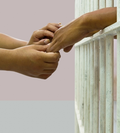 Woman comforting man in prison by holding his hand gently
