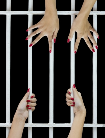 waiting convict: Woman fingers with red nails holding grip on the bars of the cage