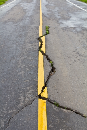 Cracks on asphalt the yellow line dividing lanes with grass  photo