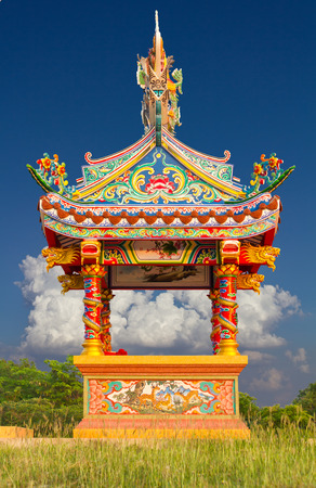 Small shrine, which is the art of China, located in the grass on cloudy sky  photo