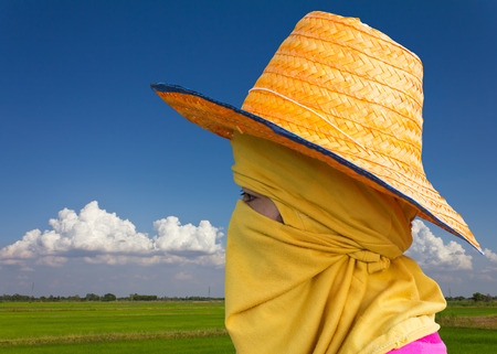 purdah: Farmer woman wearing a hat and a veil amid field and sky with clouds