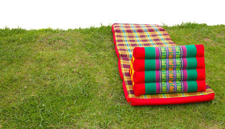 Triangle Pillow with red cloth folding mattress laid on the grass  photo