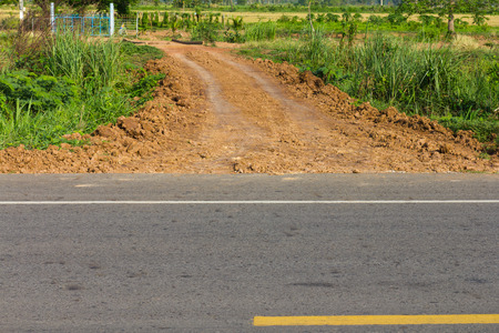 Dirt road which branches off the paved trail to the field of agriculture