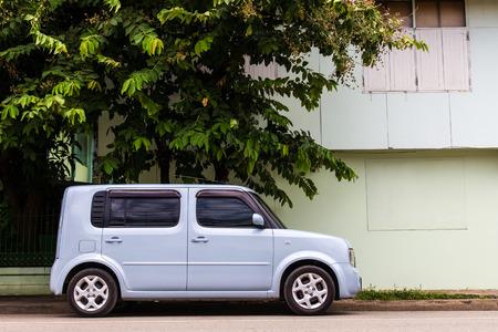 Van cars rectangular light blue four-door parked next to the house  Editorial