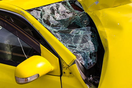 window repair: Close up of a Yellow car glass damage caused by accident