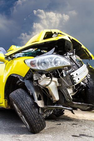 total loss:  Foreground yellow car accident demolished Cloud sky as a backdrop