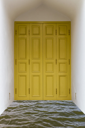 Yellow wooden door in white concrete box over the water  photo