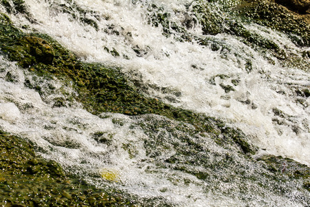 Close up of a waterfall that flows into a concrete wall stone.