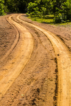 Traces of wheeled vehicles used in agriculture on a dirt road. photo