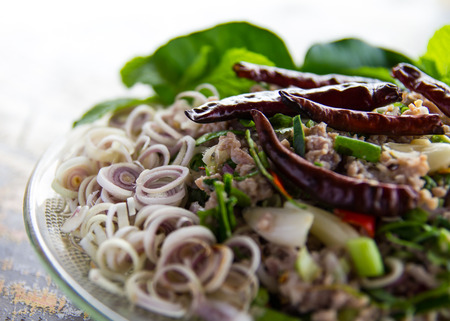 Spicy minced pork salad with dried chillies garnished with lemon grass. photo