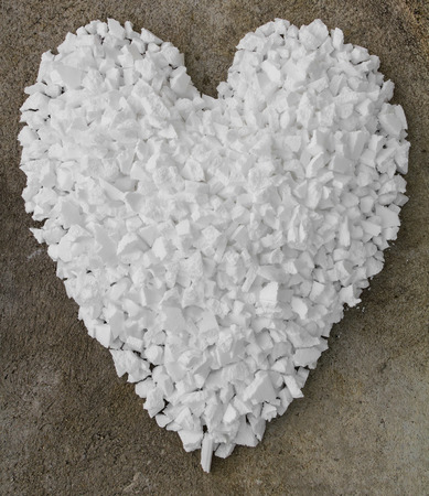 Background of little piles of scrap foam into a heart on the concrete. photo
