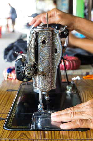 Patterns on old sewing machine and hand of a female artisans.