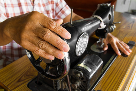 Female hand holding a rotating wheel of the sewing machine to the test. photo