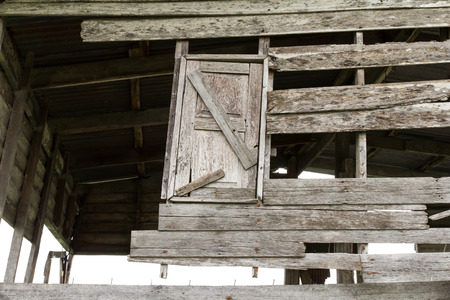 Dilapidated wooden window in the wall of a decaying old house. photo