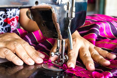empleadas domesticas: Mano de la mujer cose reparaciones rosa de tela en vieja máquina de coser.