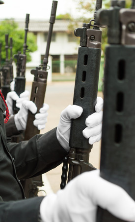 Close-up of a row of police wearing white gloves, long guns. photo