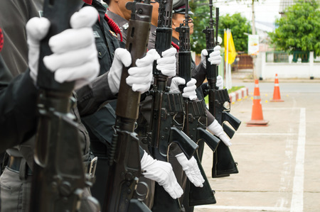 A row of police wearing white gloves holding a gun to salute.