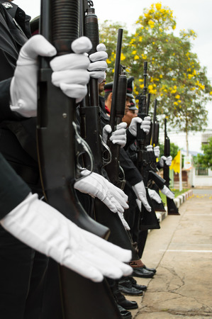 Close-up of a row of police wearing white gloves holding a gun salute. photo