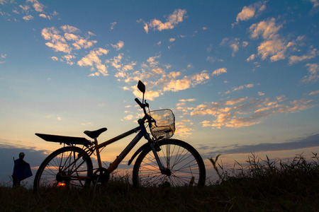 Silhouette of mountain bikes with the farmer on the grass under the beautiful sky. photo