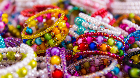 Background of colorful bead bracelets piled together so many different retailers. Stock Photo