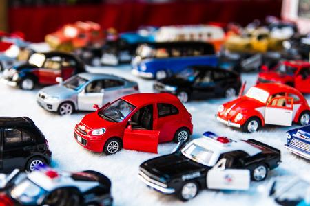 Veel kleine speelgoed auto's opgesteld op het prachtige witte stof. Stockfoto