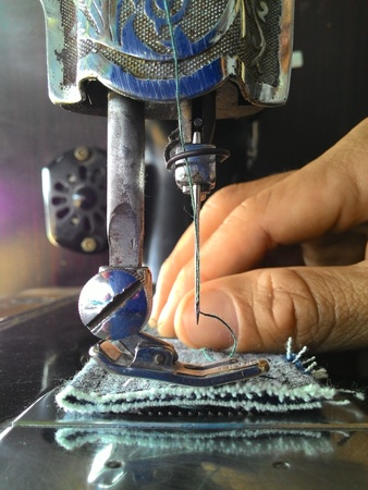 Close-up of old sewing needle with fingers Male to scrap denim. Stock Photo