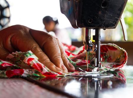 Close-up van vrouwen met een oude naaimachine steek stof mooie bloemen.