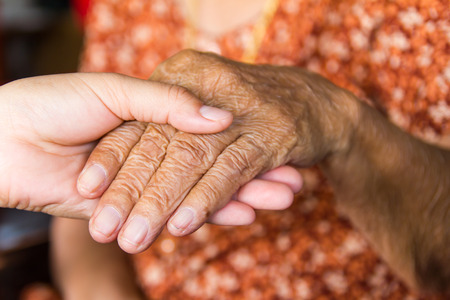 Woman hold the hand of an elderly grandmother