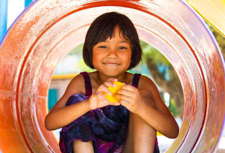 kid portrait: Thailand girls sat cheerfully colored tanks in the playground of the sole. Stock Photo