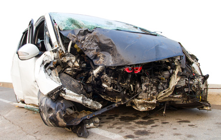 Demolished white car which collided with a tree accident severely damaged. Stock Photo