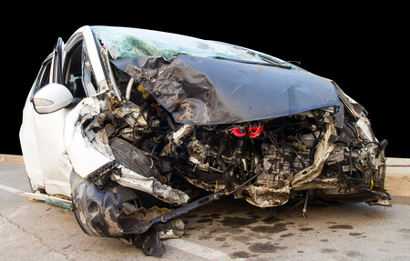 total loss: Demolished white car which collided with a tree accident severely damaged. Stock Photo